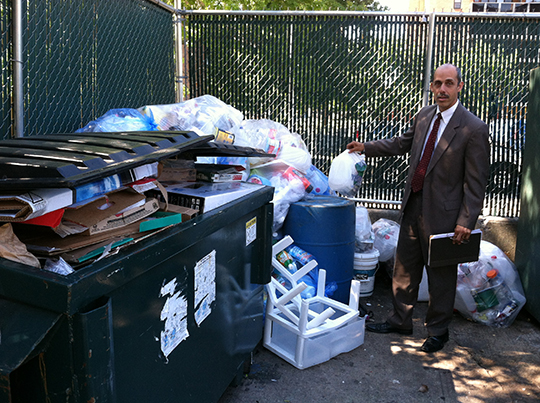 Jamie Towers General Manager, Victor Berrios, stands with the growing piles of recycling.